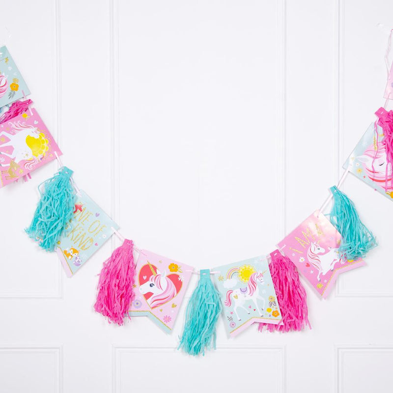 A colouful pink and blue unicorn-themed party garland with tassels and pennants
