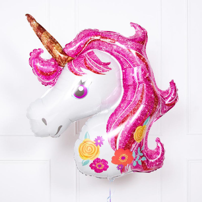 A floating unicorn-themed balloon with gold horn and pink mane