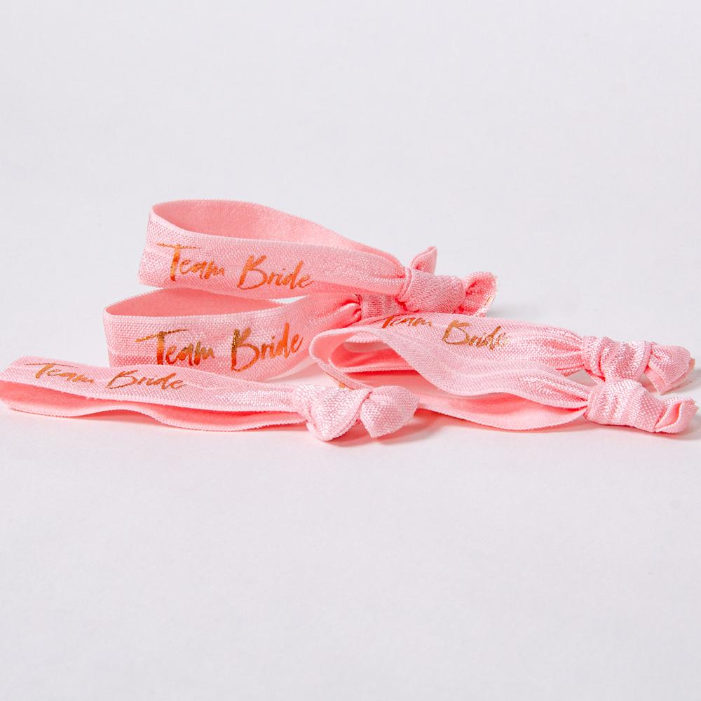 "Pile of hen party wrist bands with ""Team Bride"" written in shiny rose gold foil letters"
