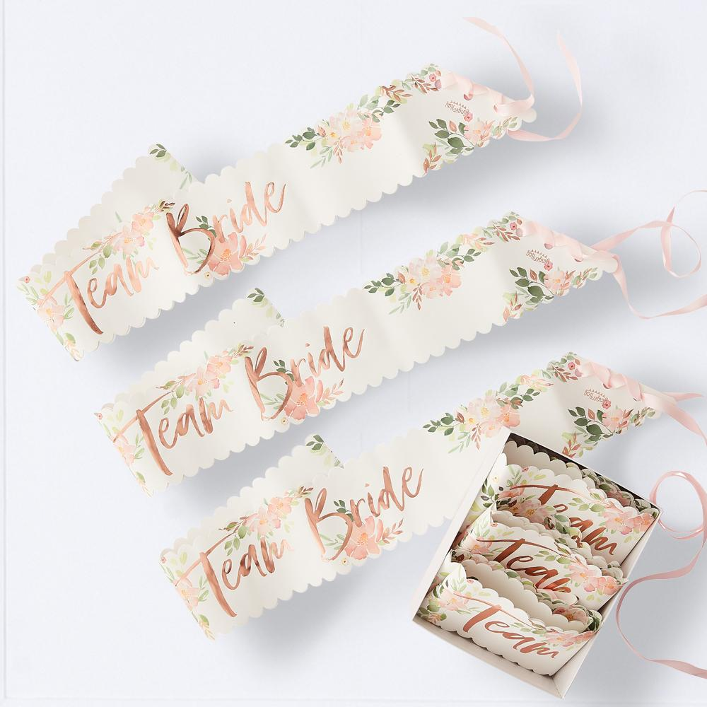 "A collection of floral hen party sashes with rose gold ""Team Bride"" phrases"
