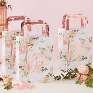 A collection of rose gold and floral featuring hen party bags with rose gold foil handles