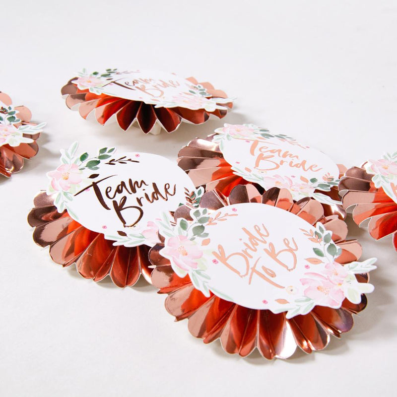Group of rose gold hen do roundels with various messages on the front