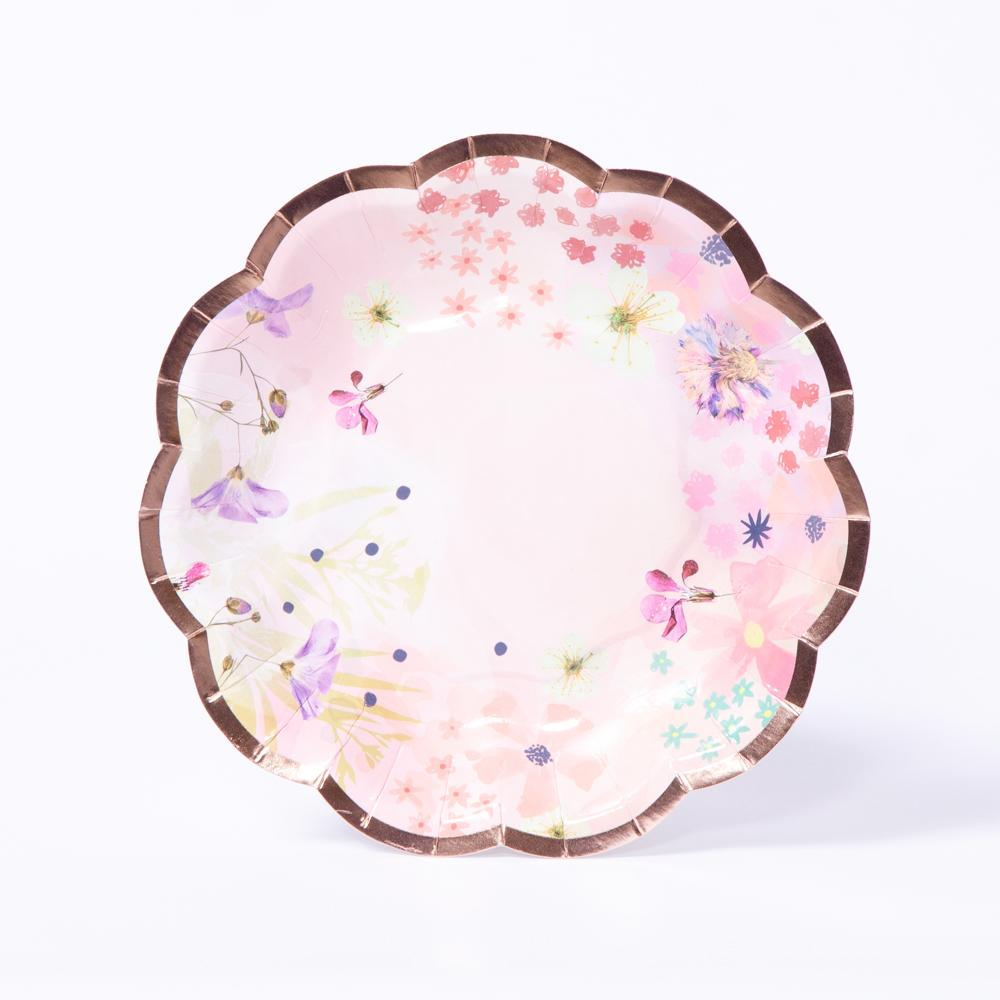 A scalloped-edge party plate with pink floral patterns and a rose gold foil trim