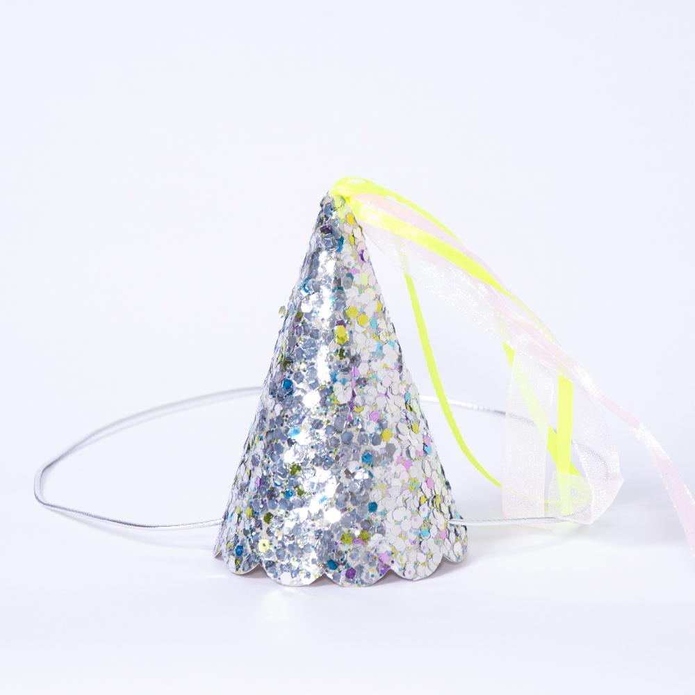 A glittery silver party hat with a yellow tassel