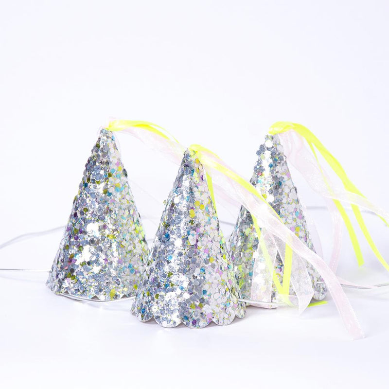 A silver, glitter-covered princess party hat with a yellow tassel and silver chinstrap