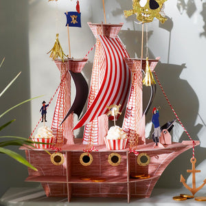 A large pirate ship party centrepiece with cupcakes placed on top