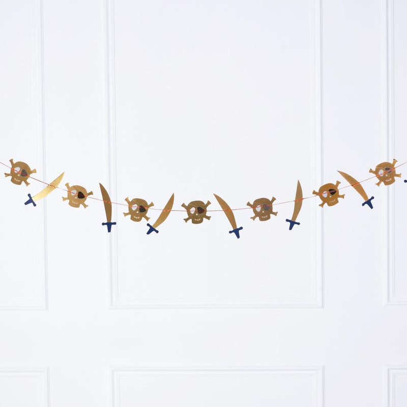 A pirate-themed party garland featuring gold cutlasses and skulls