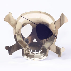 A skull and crossbones-shaped party plate covered in a glimmery gold foil finish