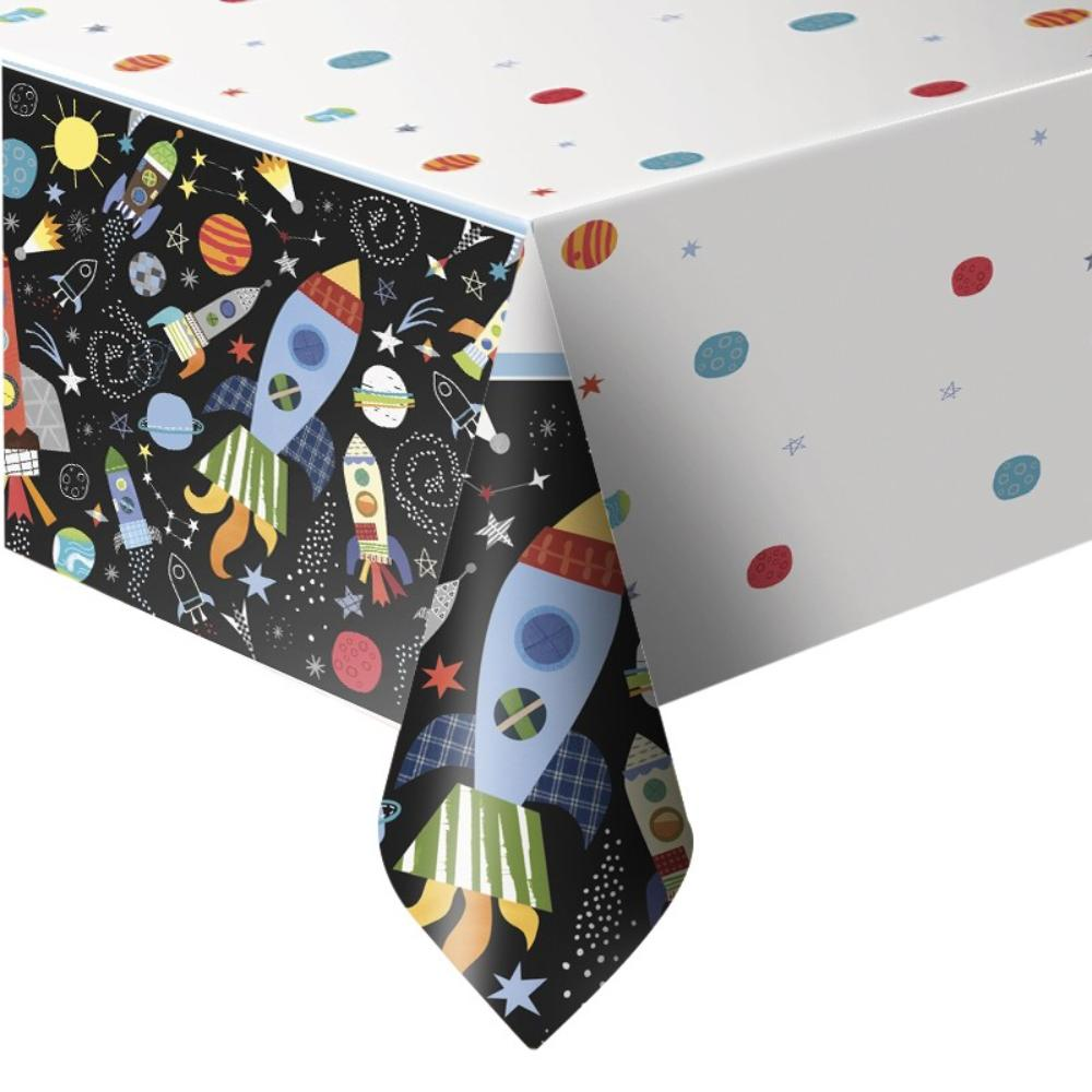 A space-themed party table cover with illustrations of rockets, planets, and stars