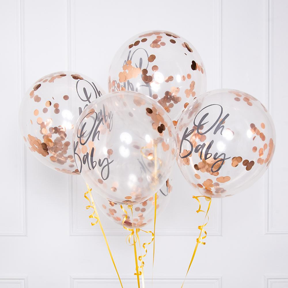 A bunch of rose gold confetti balloons tied together with gold balloon ribbon