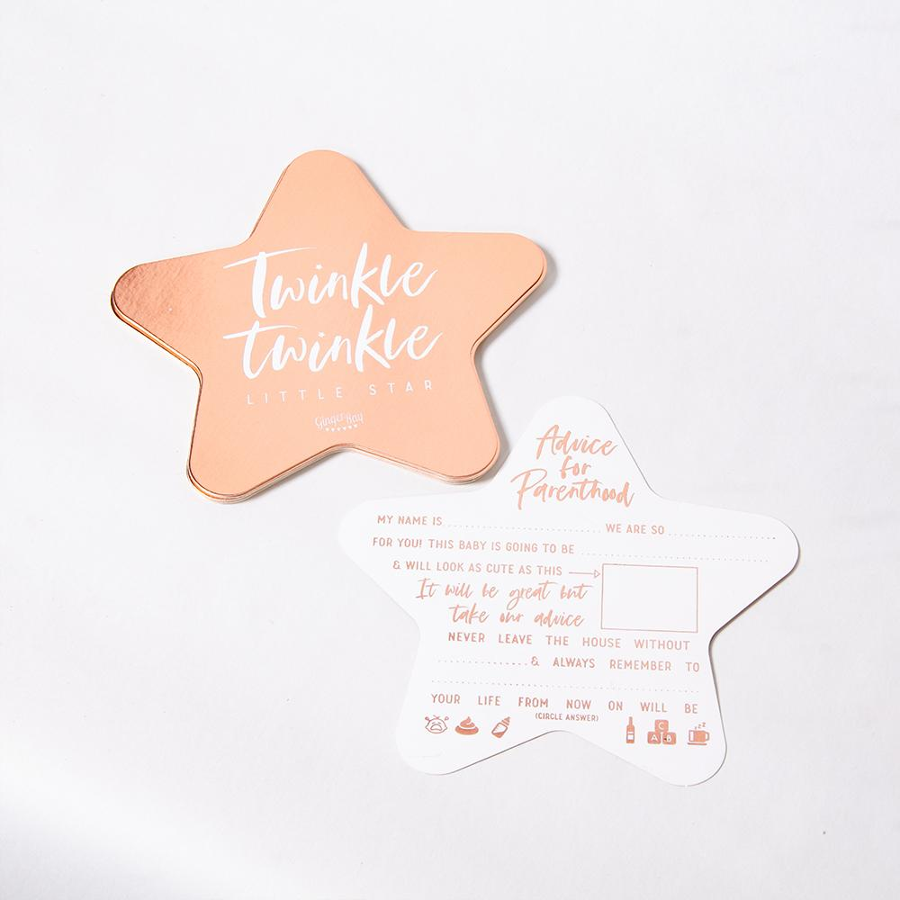 A rose gold baby shower advice card in the shape of a star