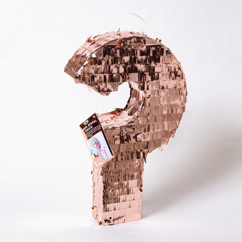 A baby shower pinata in the shape of a question mark with rose gold tassels