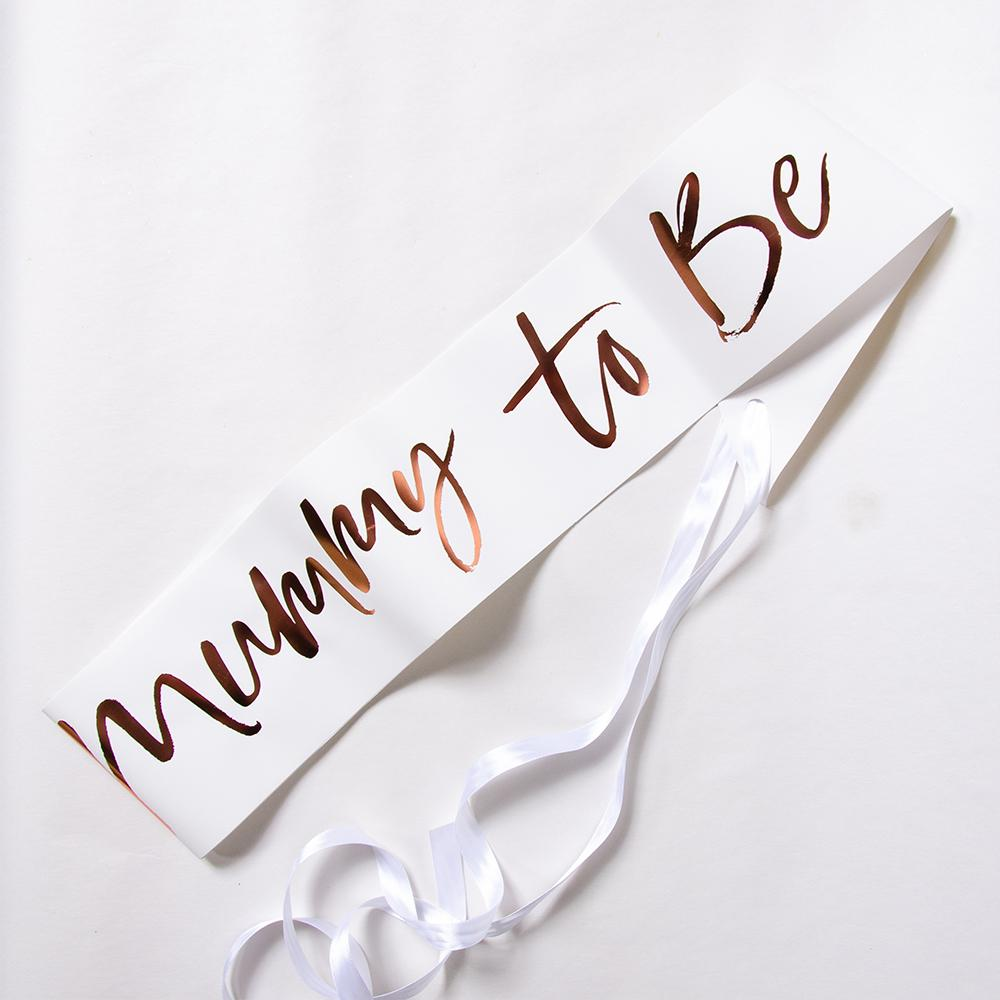 A white baby shower sash with a rose gold foil text saying Mummy-to-be