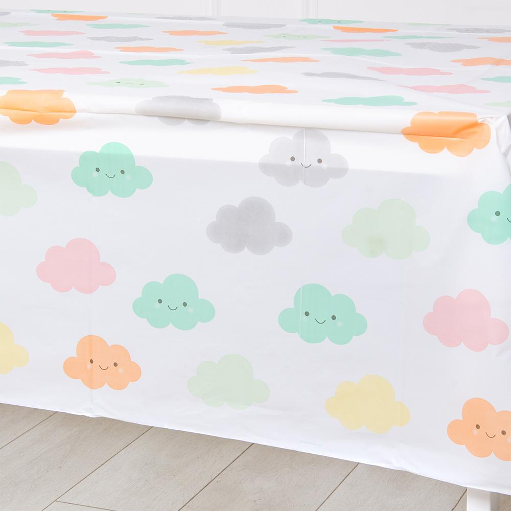 A baby shower table cover covered in illustrations of happy clouds