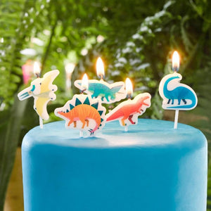 5 dinosaur-shaped party cake candles on top of a blue birthday cake