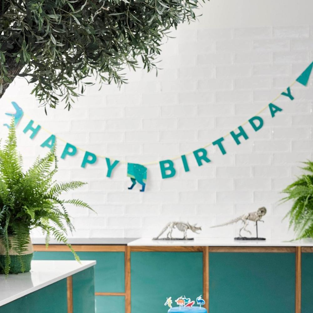 A T-Rex themed dinosaur party garland with a Happy Birthday greeting