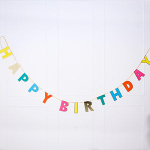 "A party garland with the phrase ""Happy Birthday"" written in multicoloured letters"