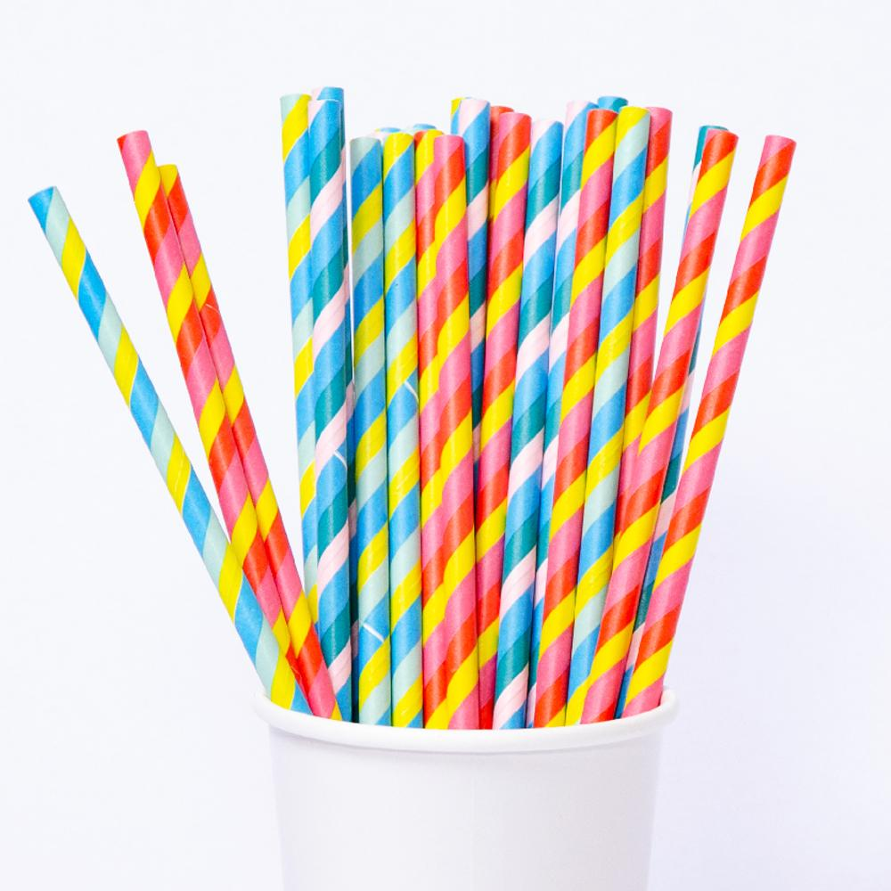 A cup filled with paper party straws with a swirly colourful design