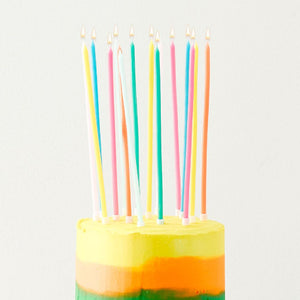 A birthday cake with super long candles in different colours
