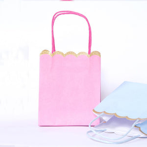 A pink and blue party bag with a scalloped, gold glittered opening