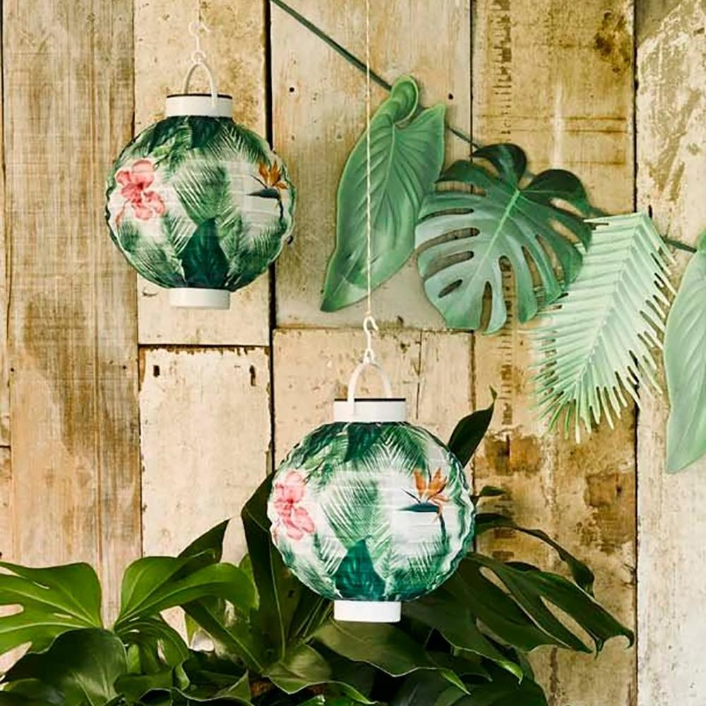 2 tropical-themed solar lanterns hung up near a party garland and house plant