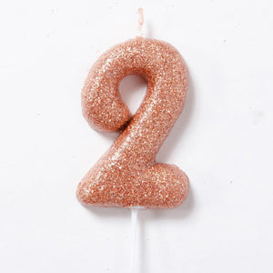 A rose gold glitter number 2 cake candle