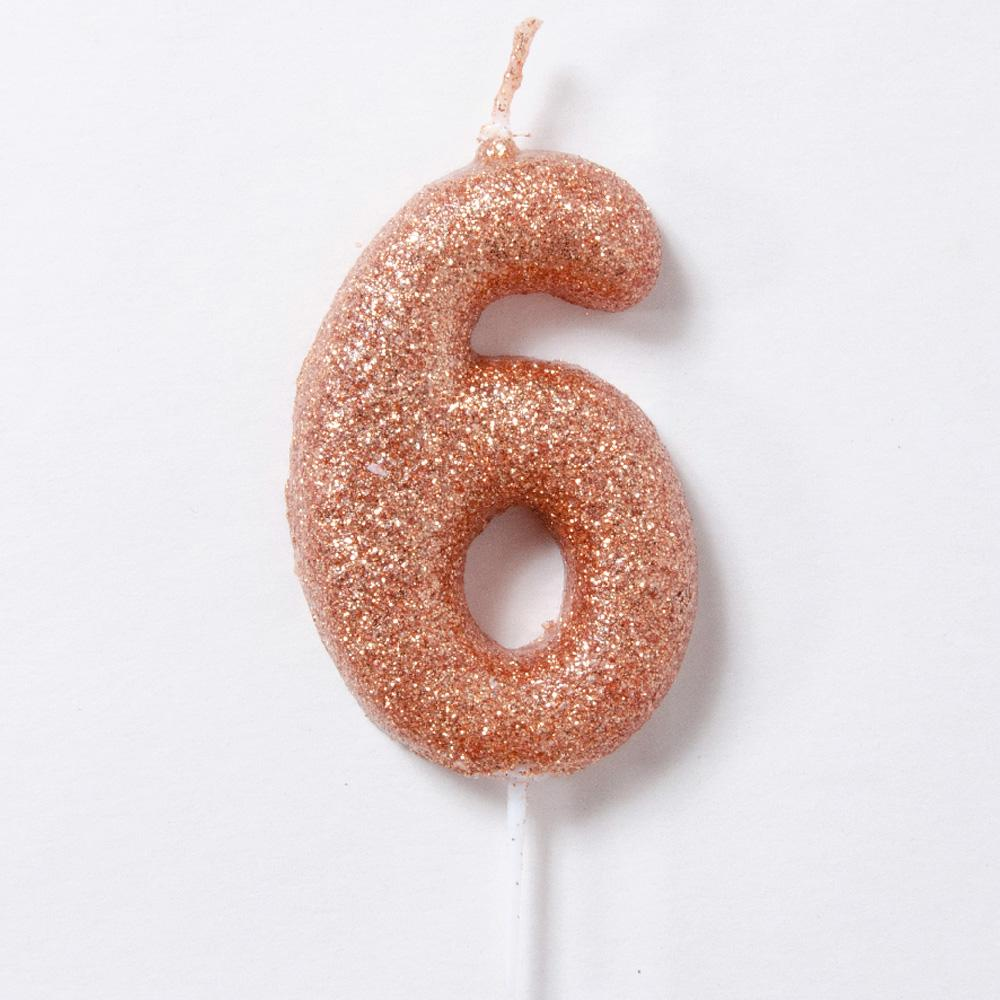 A rose gold glitter number 6 cake candle