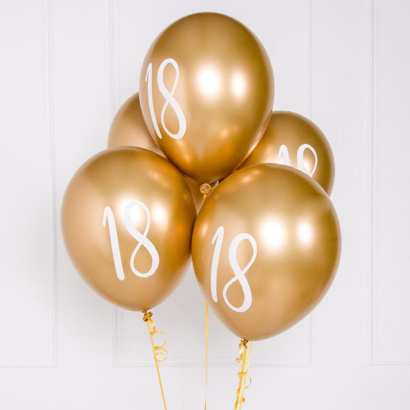 "A bunch of metallic gold latex milestone party balloons with a number ""18"" on it"