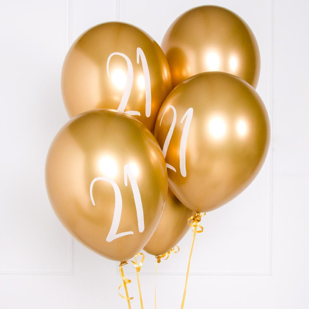 "A bunch of metallic gold latex milestone party balloons with a number ""21"" on it"