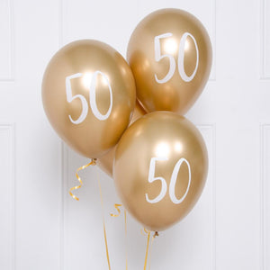 "A bunch of metallic gold latex milestone party balloons with a number ""50"" on it"