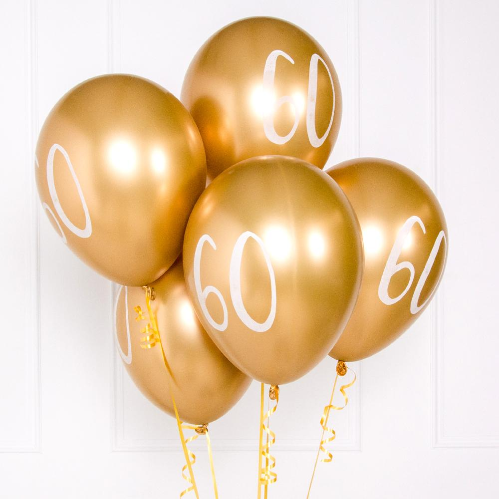 "A bunch of metallic gold latex milestone party balloons with a number ""60"" on it"