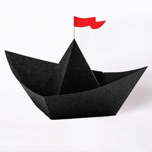 A small black paper pirate boat with a little red flag