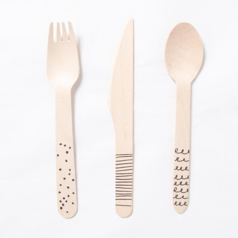 A wooden fork, spoon, and knife with a pirate doodle design on the handle