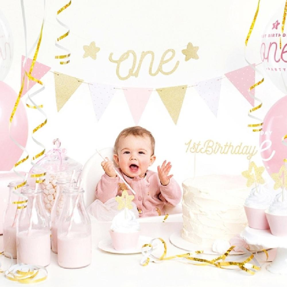 A baby surrounded by pink and gold 1st birthday party decorations