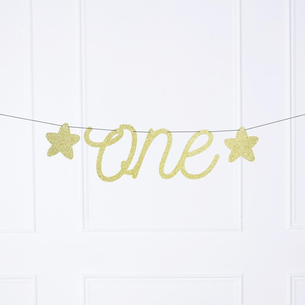 "A 1st birthday party banner with a glimmery gold foil ""one"" phrase and 2 gold stars"