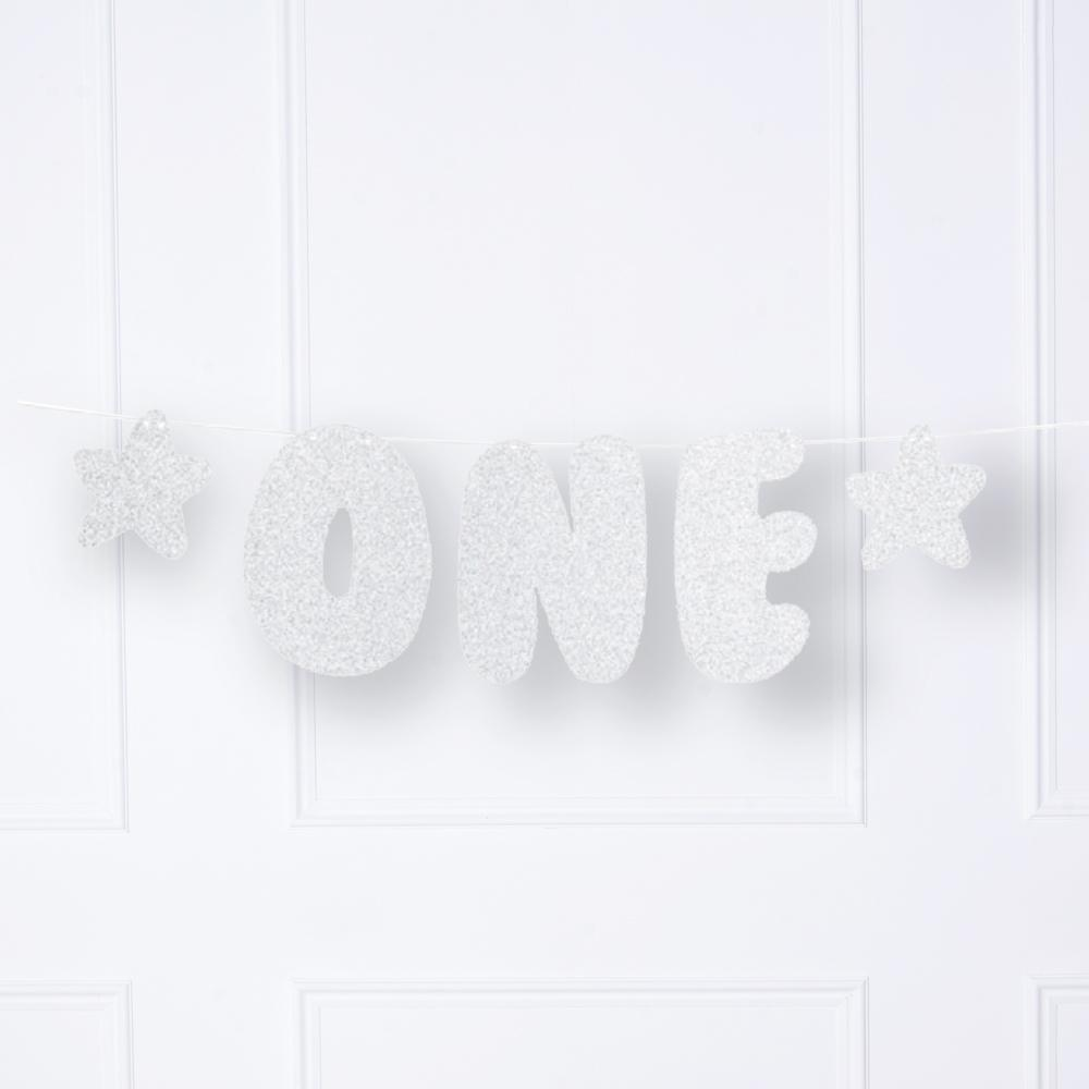 "A silver 1st birthday phrase banner with a ""one"" phrase and 2 glittery stars"
