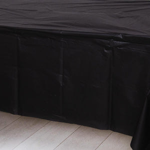A black plastic party table cover spread over a table