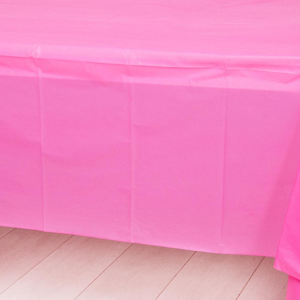 A bright pink plastic party table cover spread over a table
