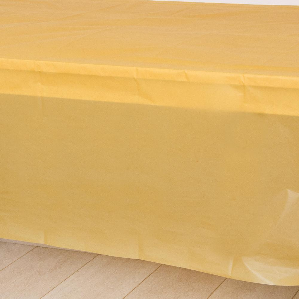 A gold plastic party table cover spread over a table