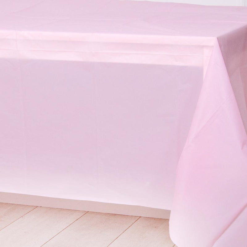 A pale pink plastic party table cover spread over a table
