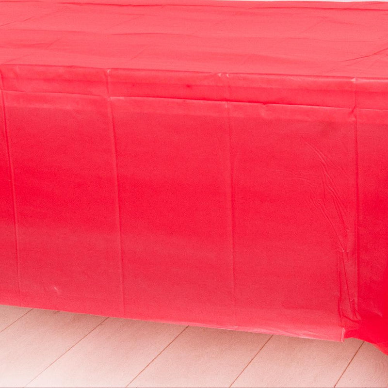 A red plastic party table cover spread over a table