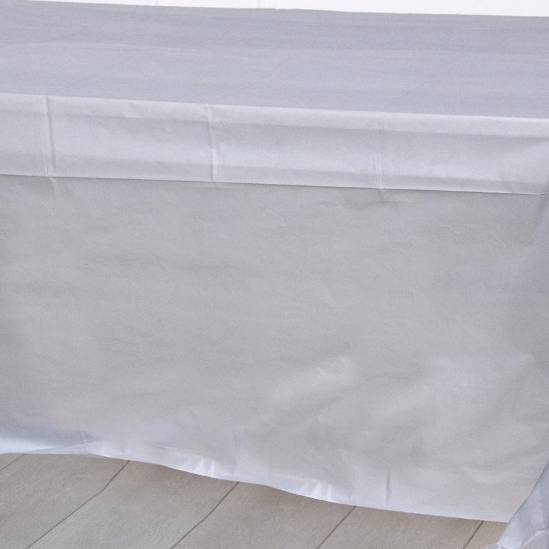 A silver plastic party table cover spread over a table