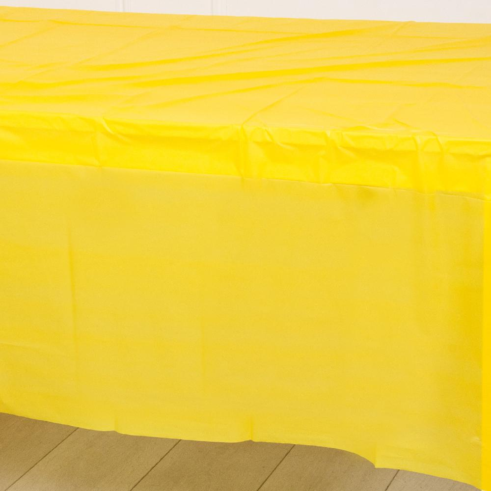 A sunflower yellow plastic party table cover spread over a table
