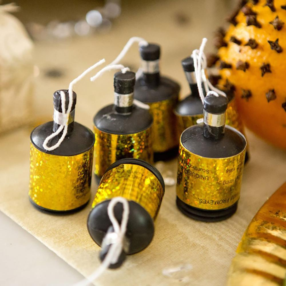 A handful of gold-foil party poppers on a party table