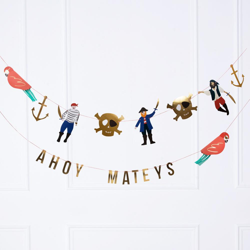 "A pirate-themed party garland with pirate shapes and a phrase saying ""Ahoy Mateys"""