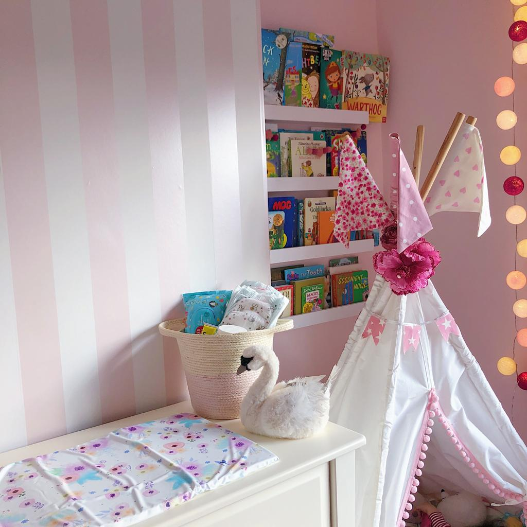 Pink baby girl nursery with teepee and floral mini changing mat