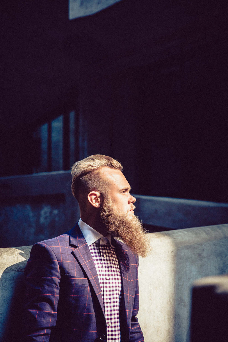 bearded white man starring in to nothing wearing designer suit