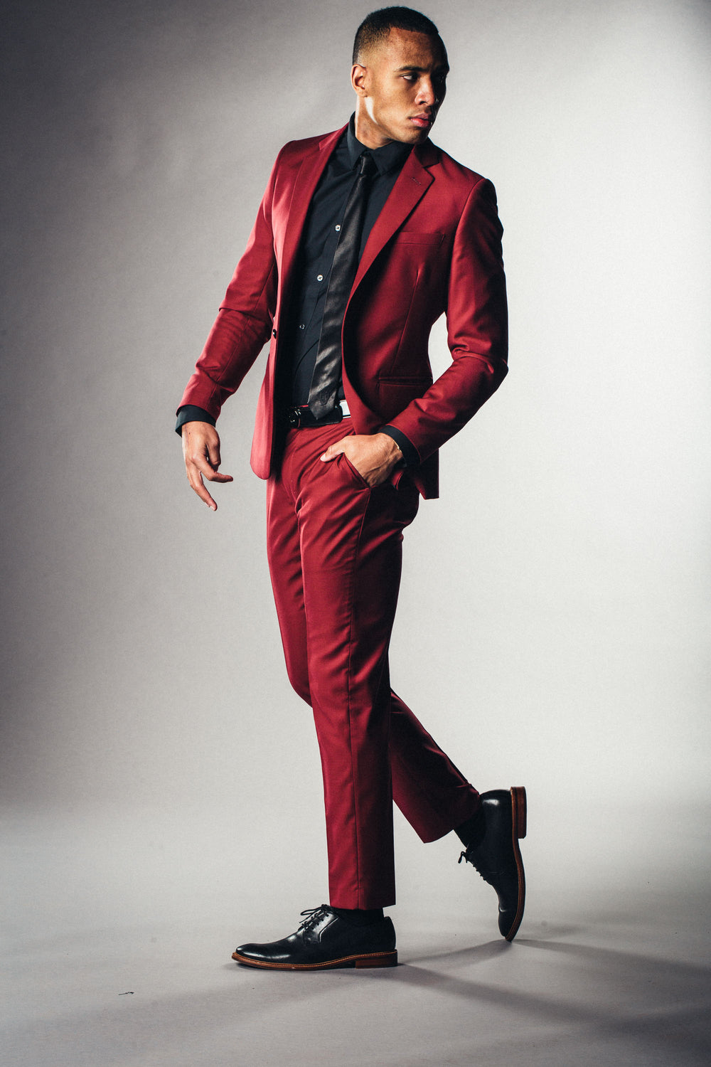Handsome black athletic looking man in bold red custom made suit