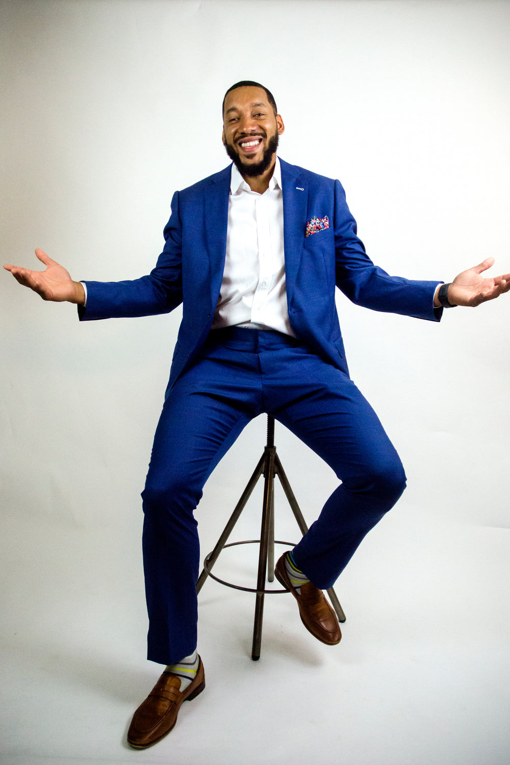 Bold blue suit on Amir Caldwell who is sitting on a stool smiling