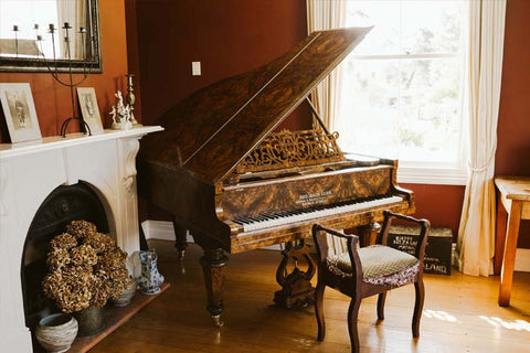 an antique baby grand piano near a window in an old house